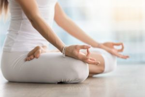 Young attractive yogi woman practicing yoga, sitting in Padmasana, exercise, Lotus pose with mudra, working out, wearing white sportswear, indoor, meditation session near window. Midsection close up